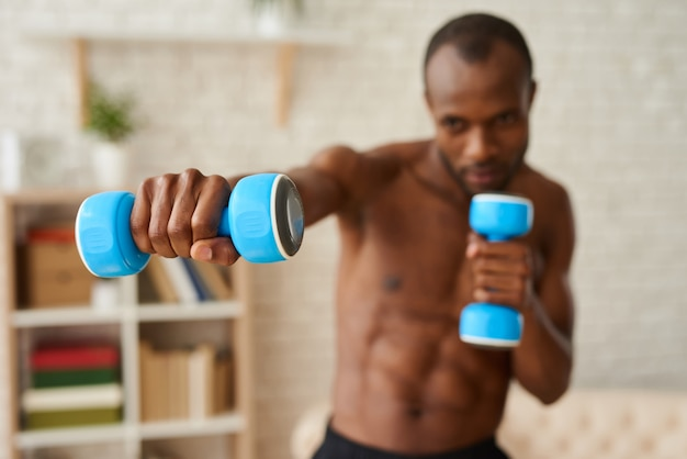 Uomo africano che fa esercizi di boxe con manubri.