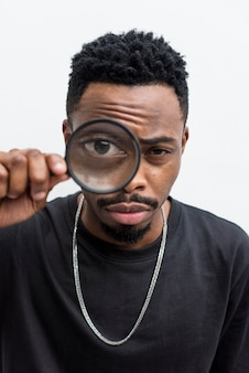Uomo africano che gioca con una lente di ingrandimento