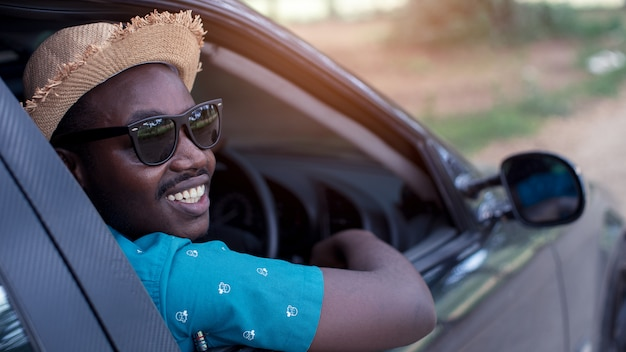Uomo africano che guida e che sorride mentre sedendosi in un'automobile