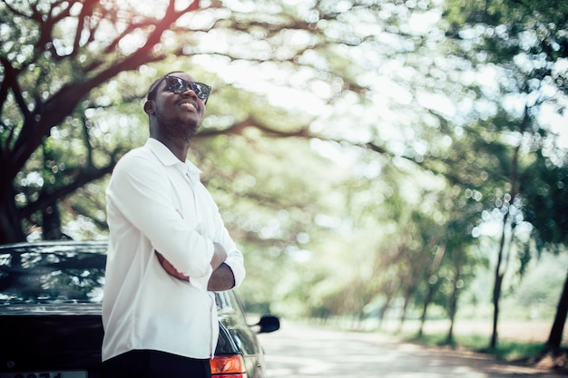 Uomo africano che indossa una camicia bianca e occhiali da sole in piedi in macchina