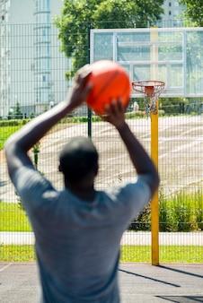 Uomo africano che lancia una palla nel cerchio