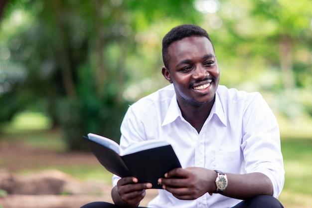 Uomo africano che legge un libro nel parco