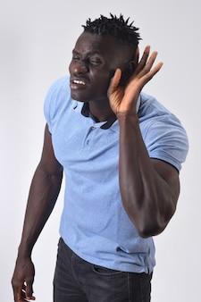 Uomo africano che mette una mano sul suo orecchio perché non può sentire su fondo bianco