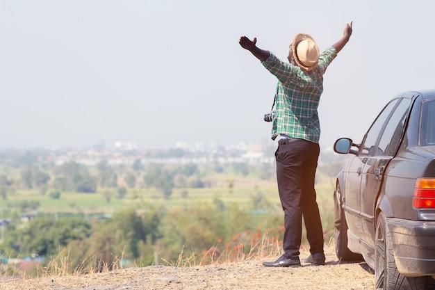 Uomo africano che si leva in piedi in cima alla scogliera della roccia con l'automobile