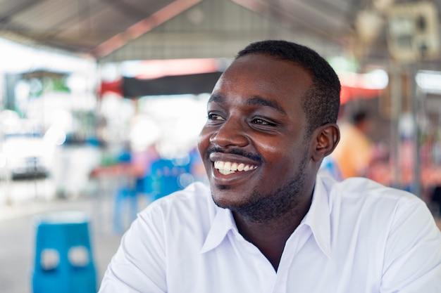 Uomo africano che sorride con la camicia bianca di usura
