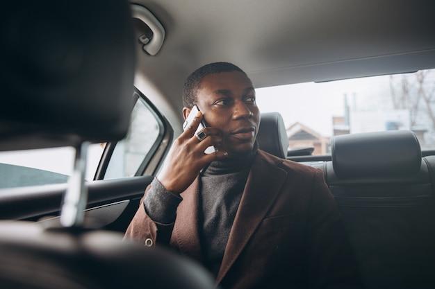 Uomo africano che utilizza smartphone mentre sedendosi sul sedile posteriore in automobile.