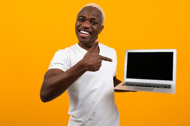 Uomo africano con lo schermo sorridente del computer portatile della tenuta dei capelli bianchi in avanti con la disposizione che indica lo schermo su giallo