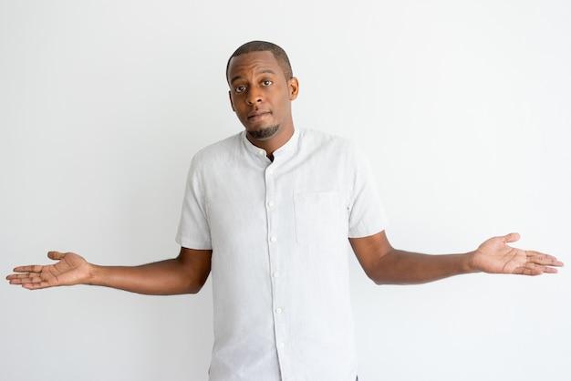 Uomo africano confuso con la barba che scrolla le spalle le spalle e che esamina macchina fotografica.