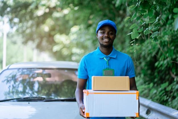 Uomo africano del corriere di consegna postale dell'uomo di sorriso davanti all'automobile che consegna pacchetto