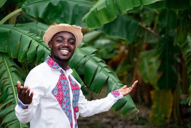 Uomo africano dell'agricoltore che sta con il banano in azienda agricola organica concetto di coltivazione o di agricoltura