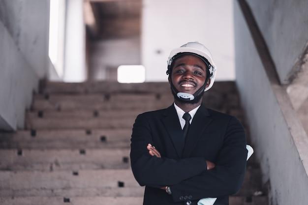 Uomo africano dell'ingegnere che sorride con una grande risata naturale alla costruzione non finita