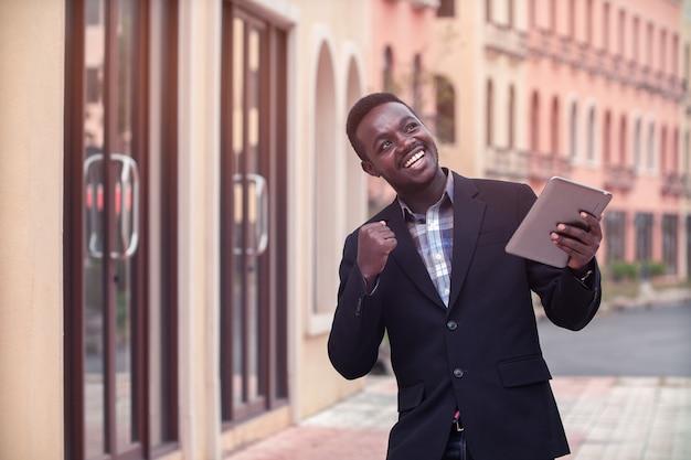 Uomo africano di affari che celebra successo con mantenendo le braccia alzate ed esprimendo azione di positività
