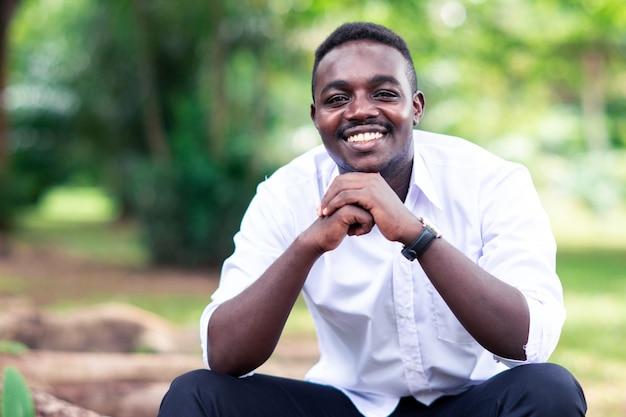 Uomo africano di affari in camicia bianca che sorride e che si siede fuori con gli alberi verdi su fondo.