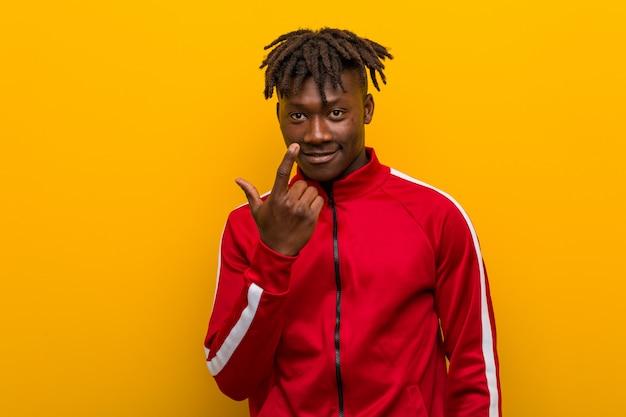 Uomo africano di giovane forma fisica che indica con il dito voi come se l'invito si avvicini.