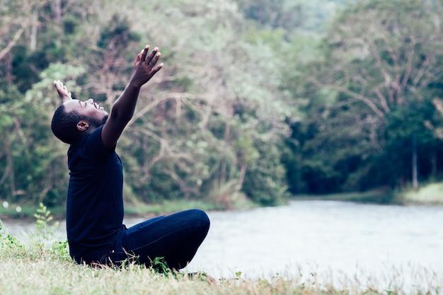 Uomo africano di libertà godendo e rilassarsi con in verde sfondo naturale.