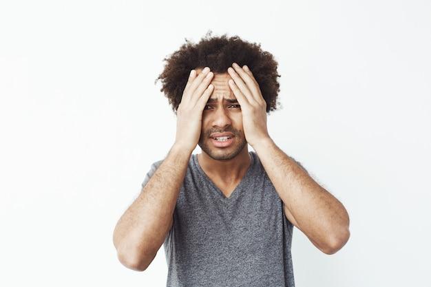 Uomo africano dispiaciuto afferrare il viso con le mani.