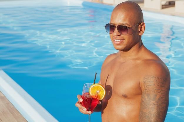 Uomo africano felice bello che sorride, distogliendo lo sguardo pensieroso, rilassandosi a bordo piscina. uomo attraente che gode del cocktail alla piscina