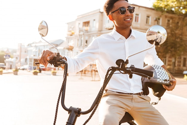 Uomo africano felice che si siede sulla motocicletta moderna all'aperto e distogliere lo sguardo