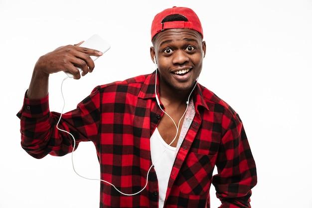 Uomo africano felice stupito che ascolta la musica dal telefono cellulare