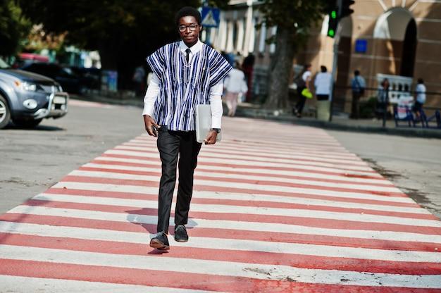 Uomo africano in vestiti e vetri tradizionali che cammina all'attraversamento con l'affare dell'africa del telefono cellulare e del computer portatile.