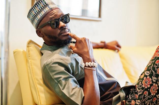 Uomo africano ricco che si siede sul sofà nel suo appartamento. ritratto di riuscito uomo di colore al coperto.