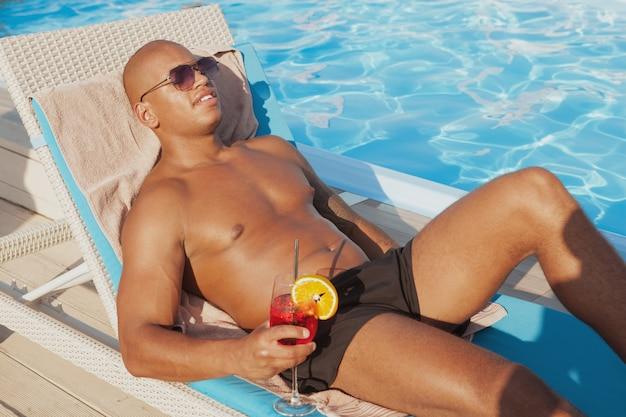 Uomo africano rilassato attraente che gode del prendere il sole, bevendo un drink a bordo piscina. uomo atletico bello che si abbronza vicino alla piscina, spazio della copia