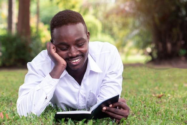 Uomo africano sdraiato sull'erba e leggendo un libro
