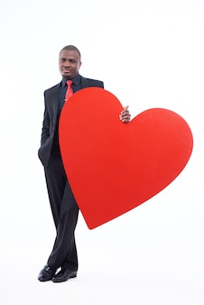 Uomo africano serio e bello che tiene grande cuore rosso