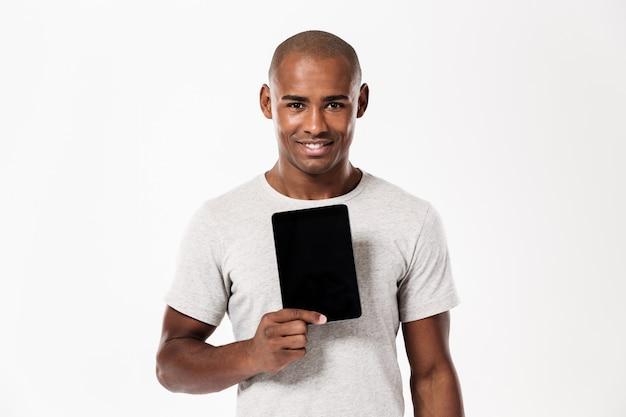 Uomo africano sorridente che mostra lo schermo e lo sguardo di computer in bianco della compressa