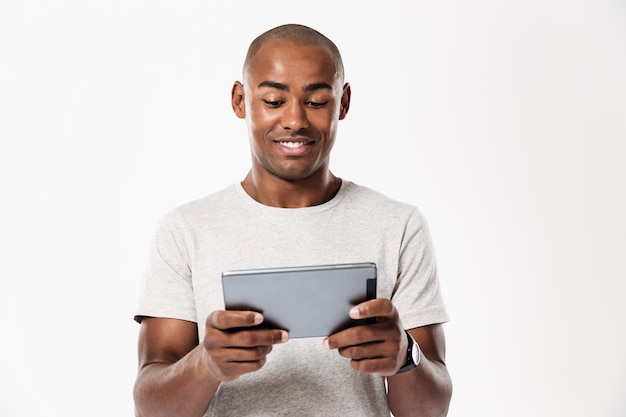 Uomo africano sorridente che per mezzo del computer della compressa