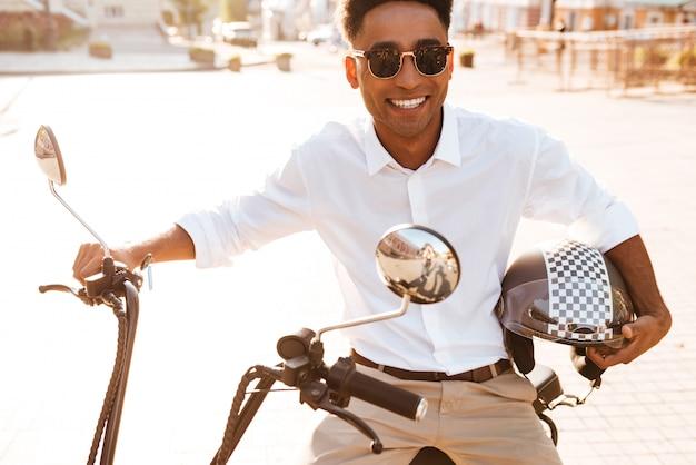 Uomo africano sorridente che si siede sulla motocicletta moderna all'aperto e che esamina la macchina fotografica