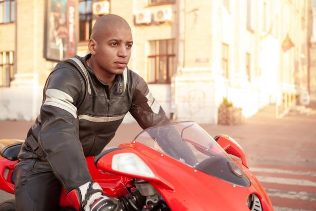 Uomo africano su una moto sportiva in città
