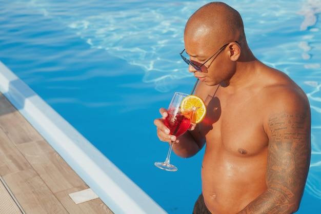 Uomo africano tatuato atletico che sorseggia la sua bevanda, rilassandosi vicino alla piscina, spazio della copia. giovane uomo godendo le sue vacanze estive, bevendo cocktail a bordo piscina