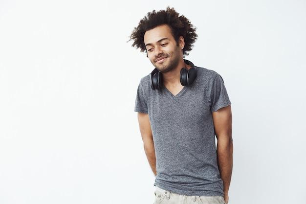 Uomo africano timido con lo sguardo sorridente delle cuffie giù.