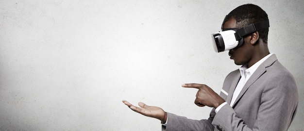 Uomo afro-americano in abbigliamento formale utilizzando le cuffie da realtà virtuale 3d per smart phone.