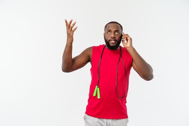 Uomo afroamericano adatto maturo che parla sul cellulare e che tiene corda elastica.