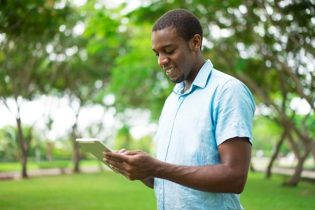 Uomo afroamericano allegro che utilizza compressa per interagire sui social media.