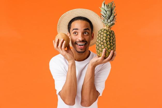 Uomo afroamericano allegro e felice, sorridente in cappello turistico, maglietta bianca, tenente noce di cocco