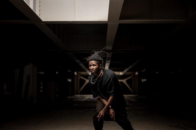 Uomo afroamericano ballante in vestiti neri