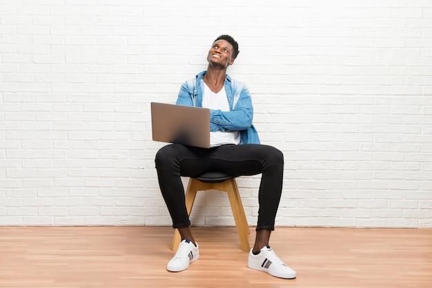 Uomo afroamericano che lavora con il suo supporto del computer portatile e che osserva in su