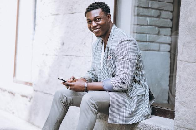 Uomo afroamericano che per mezzo del telefono