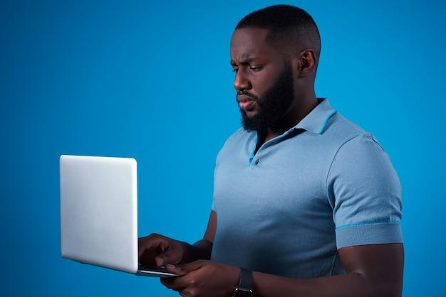 Uomo afroamericano che posa con il computer portatile isolato.