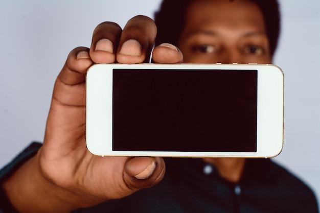 Uomo afroamericano che tiene smartphone.