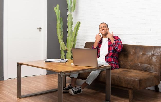 Uomo afroamericano con il computer portatile nel soggiorno che sorride con un'espressione felice e piacevole