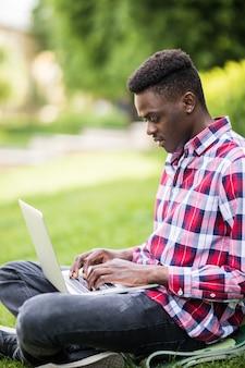 Uomo afroamericano con il computer portatile sull'erba nel parco cittadino