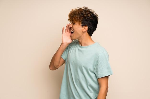 Uomo afroamericano con la camicia verde che grida con la bocca spalancata al laterale