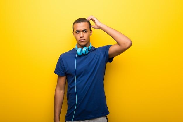 Uomo afroamericano con la maglietta blu su fondo giallo che ha dubbi mentre graffiando si dirige