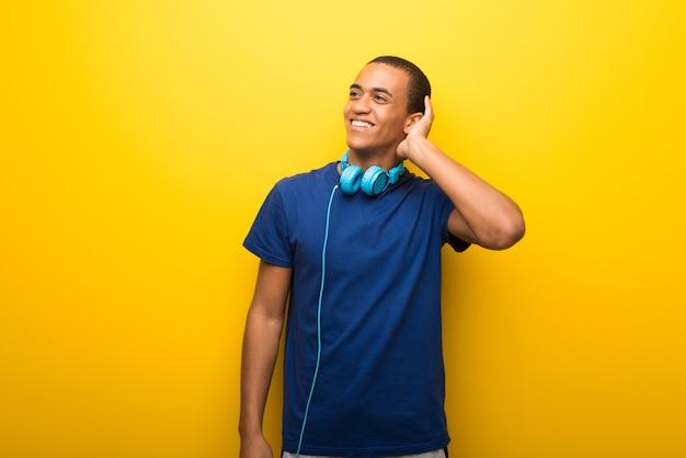 Uomo afroamericano con la maglietta blu su fondo giallo che pensa un'idea mentre graffiando si dirige