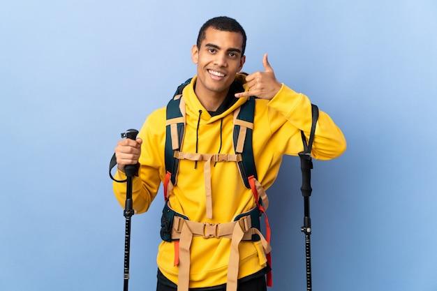 Uomo afroamericano con lo zaino e pali di trekking sopra la parete isolata che fa gesto del telefono. richiamami segno