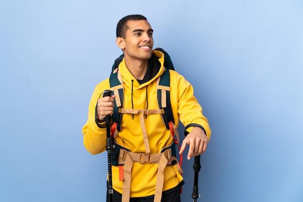 Uomo afroamericano con lo zaino e pali di trekking sopra la parete isolata che pensa un'idea mentre guardando su